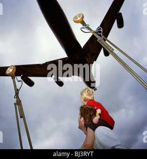 A father supports his son on his shoulders as a giant four-engined airliner passes directly overhead, about to land - Stock Photo