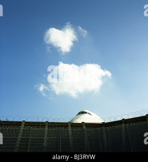 The cockpit section of a Boeing 747 jumbo jet is perceived peering over the barbed-wire perimeter fence at Heathrow - Stock Photo