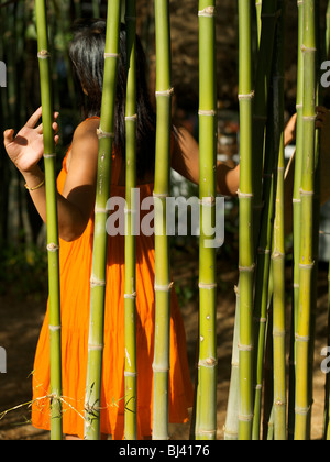 Thai lady in orange summer dress with straw hat walking in the jungle - Stock Photo