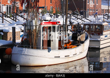 Fishing boat in the harbour of Heiligenhafen in winter on the Baltic Sea coast, Kreis Ostholstein district, Schleswig - Stock Photo