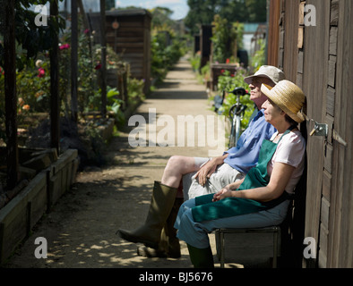 Senior couple resting in an allotment - Stock Photo