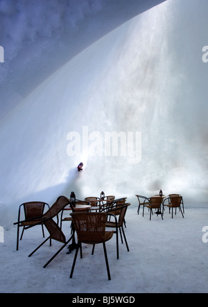Young boy looking inside to a cafe, made of snow and ice,  from a hole on the thin snow wall , Finland - Stock Photo