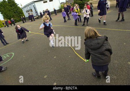 Skipping, traditional school playground game being played on the schoolyard of a primary school in Wales UK - Stockfoto