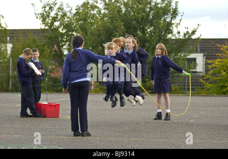 Skipping, traditional playground game being played on the schoolyard of a primary school in Wales UK - Stockfoto