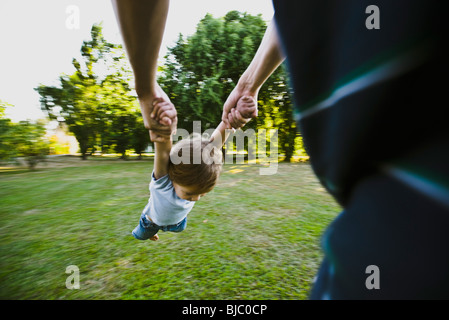 Father spinning little boy in park, cropped - Stock Photo