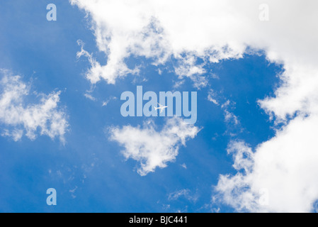 Commercial airplane flying through cloudscape - Stock Photo