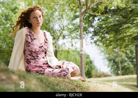 Young woman sitting on grass, looking away in thought - Stock Photo