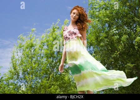 Young woman standing outdoors, holding scarf in wind - Stock Photo