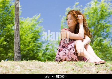 Young woman sitting outdoors, looking away in thought - Stock Photo