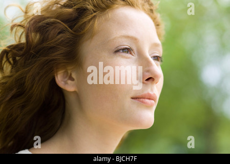 Young woman looking away in thought, portrait - Stock Photo