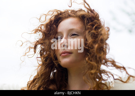 Young woman with tousled hair looking away in thought, portrait - Stock Photo
