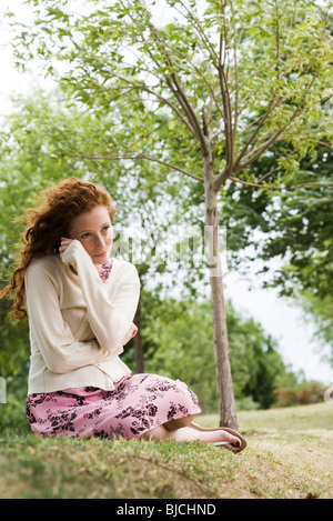 Young woman sitting outdoors, wrapping herself in cardigan - Stock Photo