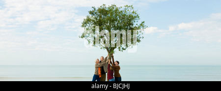Ecology concept, group of people supporting tree together - Stock Photo