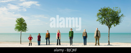 Group of people standing in row between two trees on beach - Stock Photo