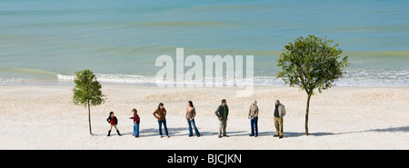 Group of people standing in row chatting between two trees on beach - Stock Photo