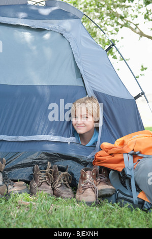 Young boy peaks out of tent - Stock Photo