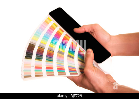 man's hands holding a colour card guide pantone - Stock Photo