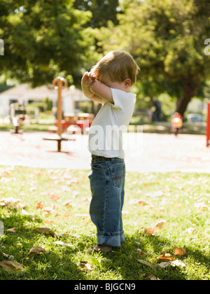 little boy playing hide and go seek - Stock Photo