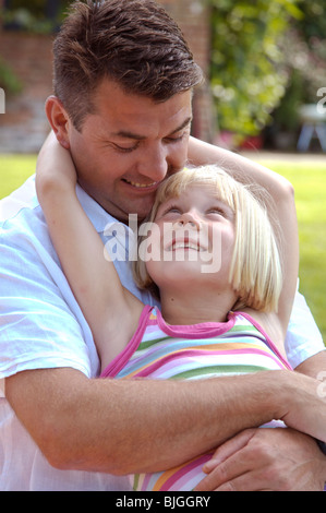 Portrait of father and daughter looking at each other smiling - Stock Photo