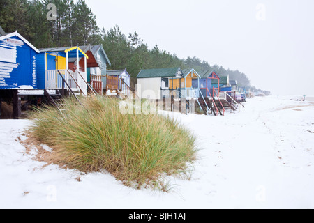 The famous colorful beach hut at Wells Next The Sea following winter snowfall on the Norfolk Coast - Stock Photo