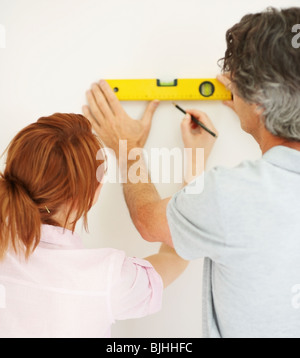 Couple marking a straight line on wall - Stock Photo