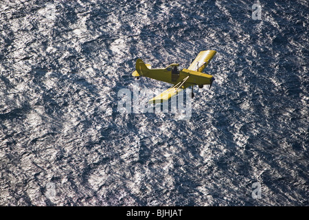 Small airplane ascending over water - Stock Photo