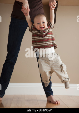 Mother swinging toddler - Stock Photo
