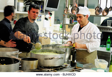 Chefs at work in a commercial kitchen - Stock Photo