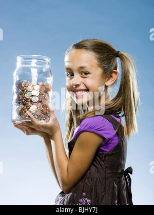 girl looking at the camera holding a jar of coins - Stock Photo