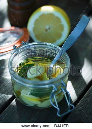Pickled garlic with lemon and herbs - Stock Photo