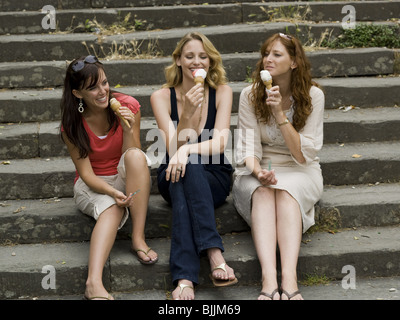 Three women sitting on steps outdoors eating ice cream cones smiling - Stock Photo