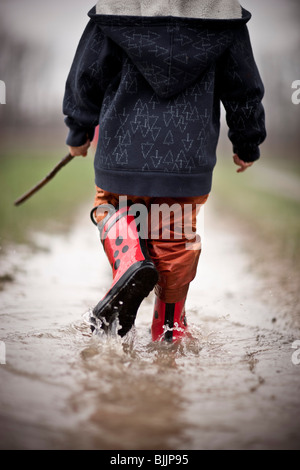 Young boy wearing rain boots walks through a puddle of water. - Stock Photo