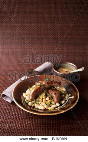 Sausages on white bean salad - Stock Photo