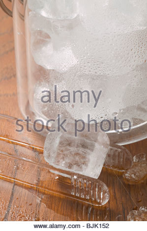 Ice cube with tongs and champagne bucket full of ice cubes - Stock Photo