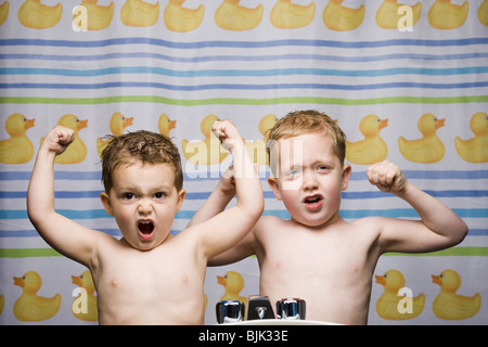 Two boys flexing muscles in bathroom - Stock Photo