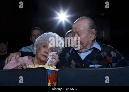 Man and woman watching movie in theater crying with popcorn - Stock Photo