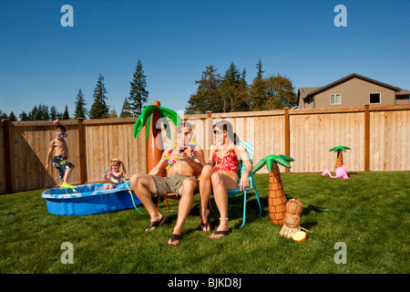 Family in yard with children's pool and cocktails - Stock Photo