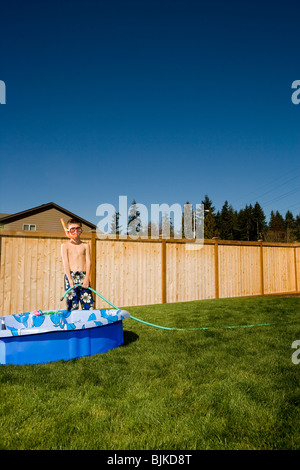 Boy in swim trunks with flippers and snorkel in yard - Stock Photo