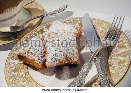 Three Beignets Topped with Powdered Sugar on a Plate; Tea - Stockfoto