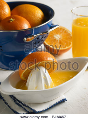 Oranges in Colander, Orange Half on Juicer, Glass of Orange Juice - Stock Photo