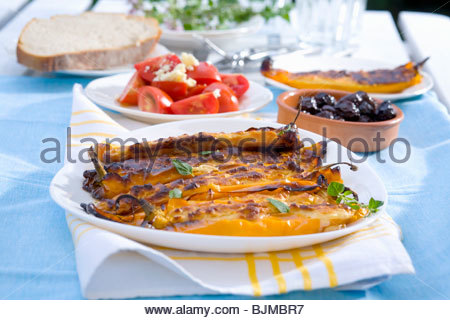 Stuffed pointed peppers, dried olives and tomato salad - Stock Photo