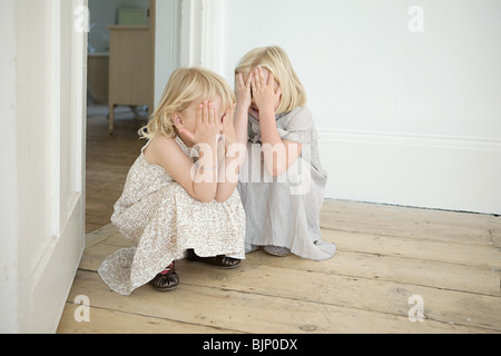 Sisters playing hide and seek - Stock Photo