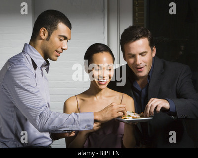 Partygoers eating - Stock Photo