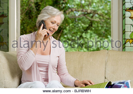 Woman on cellphone with magazines - Stock Photo