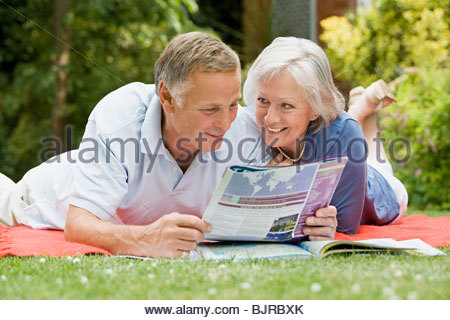 Couple looking at magazine - Stock Photo