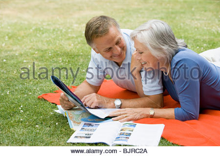 Couple looking at holiday brochures - Stock Photo