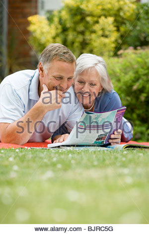 Couple looking at holiday brochure - Stock Photo