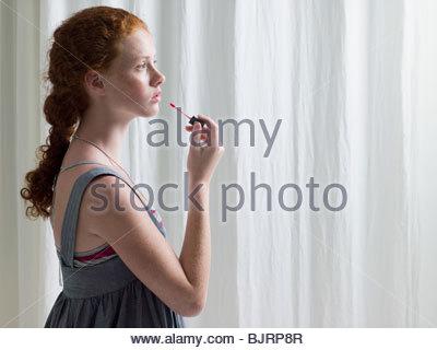 A teenage girl applying lipgloss - Stock Photo