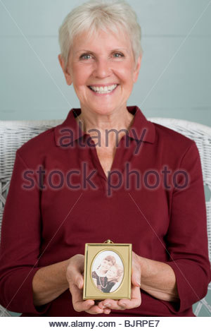 Woman holding a photograph - Stock Photo