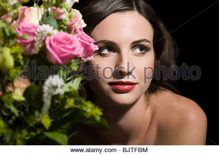 Woman behind a bunch of flowers - Stock Photo